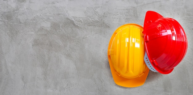 Construction helmets on concrete background.