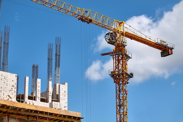 Construction of a high-rise building, the formation of cement supports and the operation of a crane against a blue sky, selective focus
