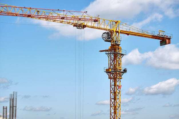 Construction of a high-rise building, operation of a tower crane against a blue sky, selective focus