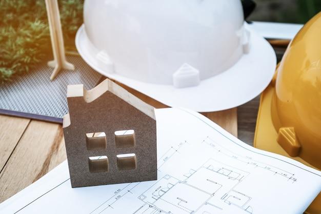 엔지니어 모자, 주택 모델 및 건축가 장비가 있는 주택 또는 콘도미니엄 프로젝트를 위한 청사진 문서에 대한 건설 주택 계획