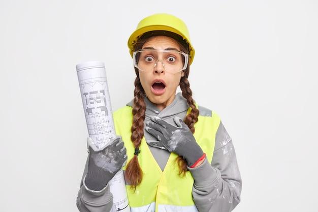 Concetto di industria delle costruzioni. il costruttore di architetti donna scioccato tiene il progetto arrotolato ha una giornata lavorativa impegnativa indossa un'uniforme protettiva stordito per scoprire qualche errore nel progetto di ingegneria