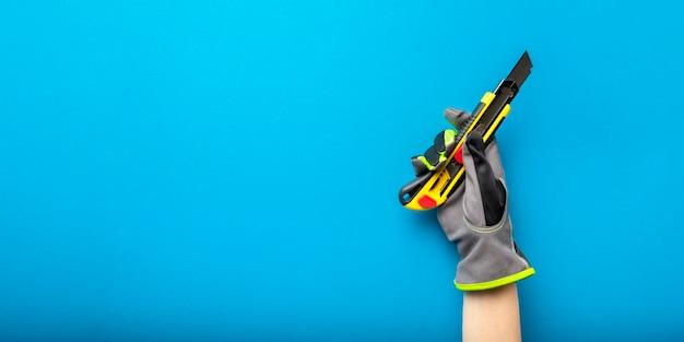 Строительный нож. канцелярский нож в руке с перчаткой на синем фоне. баннер темы строительства и ремонта. место для текста или дизайна.