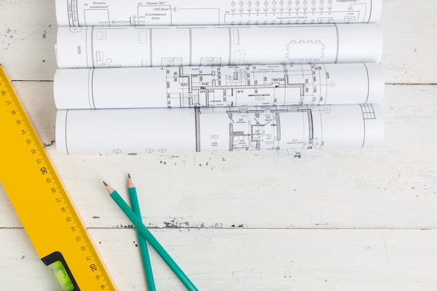 Construction level, drawings, blueprints and pencils on a white table