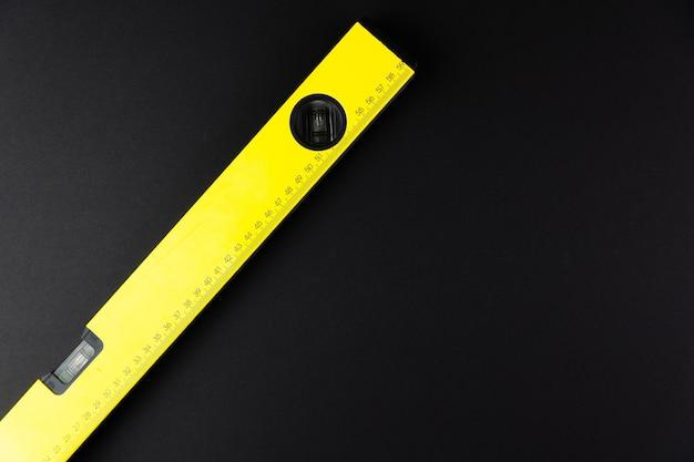 Строительный уровень желтый на черном фоне