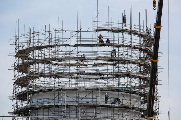 建設男性労働者は、現場の製油所に足場とクレーンを設置する石油をタンクに入れます