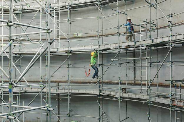 サイドタンク限定仕様に足場を設置する建設男性労働者タンクオイル