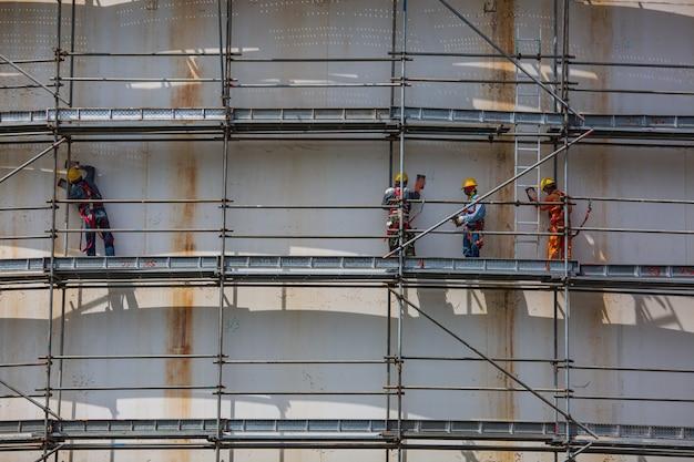 建設男性労働者は、サイトの製油所に足場を設置する石油をタンクに入れます