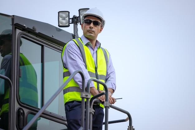 掘削機屋外サイト、産業マネージャーと建設男性ドライバー Premium写真