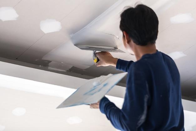 Construction man worker plaster gypsum ceiling for interior build gypsum board ceiling