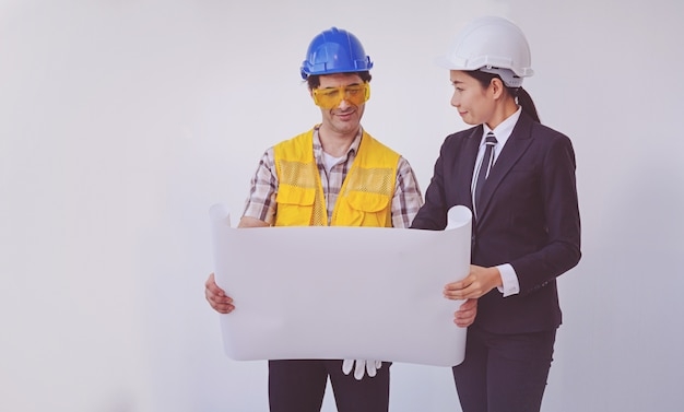 Construction manager and engineer looking at blueprints