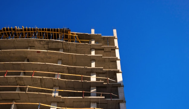 Construction of a modern building. residential building under construction against blue sky background photo