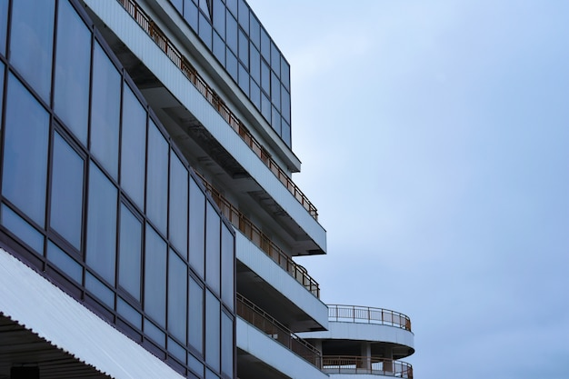 The construction of a modern building with parking from glass and long balconies