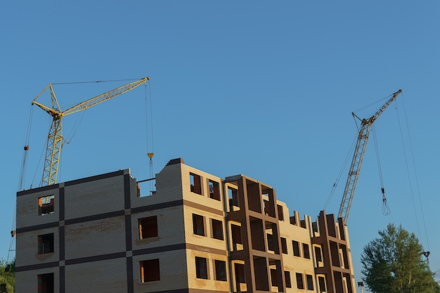 The construction of a new apartment building against the background of a clear sky.
