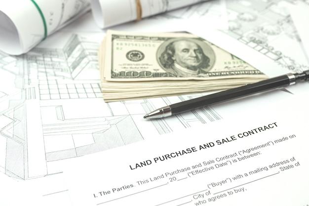 建築図面、オフィスデスクの背景写真による土地の新しい区画での建物の建設