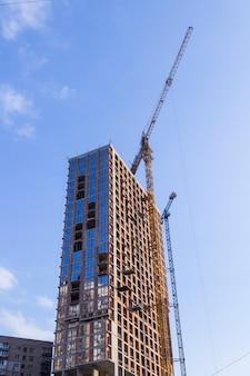 高層ビル、建設用クレーンの建設。青空。