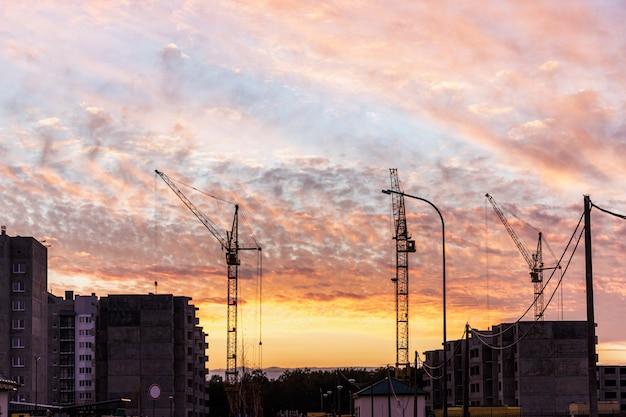 타워 크레인을 사용하여 일몰에 패널 프레임 하우스 건설. 뒷등. 주거용 건물 건설에 밤에 일하십시오.
