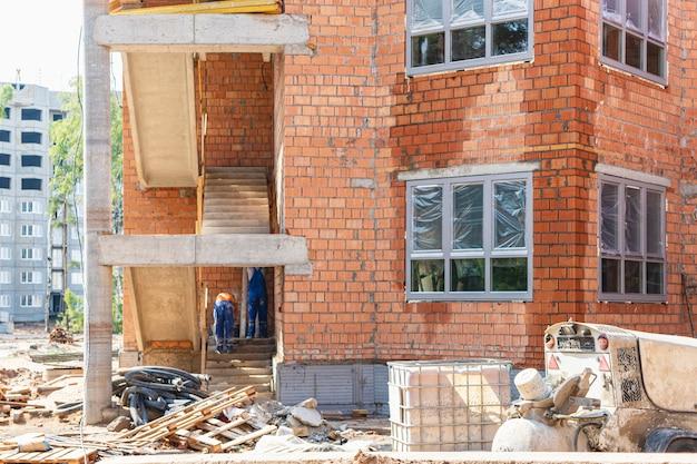 Строительство многоэтажного дома из красного кирпича. использование строительных лесов при строительстве дома. промышленное и гражданское строительство. безопасность строительства.