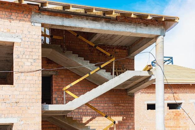 Строительство многоэтажного дома из красного кирпича. использование строительных лесов при строительстве дома. промышленное и гражданское строительство. лестница железобетонная.
