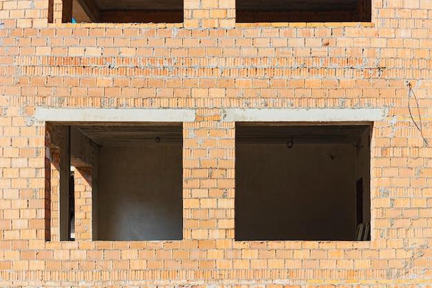 Строительство многоэтажного дома из красного кирпича. оконные проемы в строящемся доме. промышленное и гражданское строительство. подготовка к установке окон.