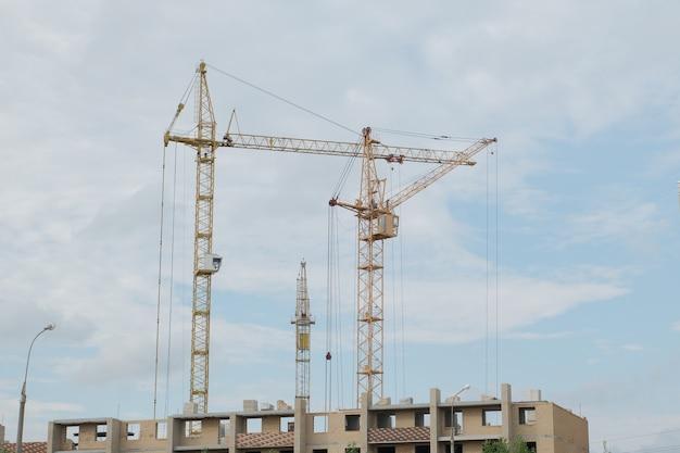 Строительство новых высотных домов строительными кранами.