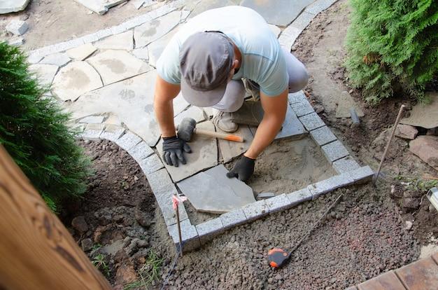 Устройство тротуара возле дома. каменщик укладывает бетонные блоки для мощения тротуара.