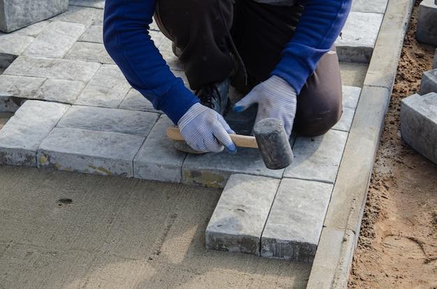 家の近くの舗装の建設。煉瓦工は、歩道舗装を構築するためのコンクリート舗装石ブロックを配置します