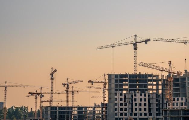 Строительство жилых домов летним вечером. многие краны в эксплуатации Premium Фотографии