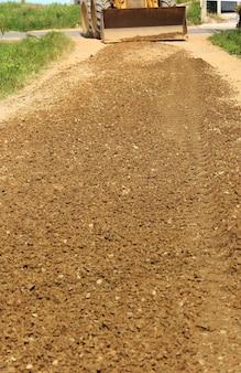 Устройство дорожного покрытия гравийным грунтом.
