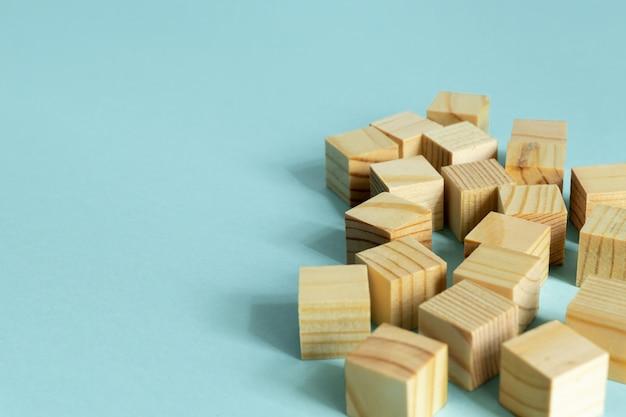 コピースペースと青色の背景に木製キューブの構築。デザインのモックアップ構成