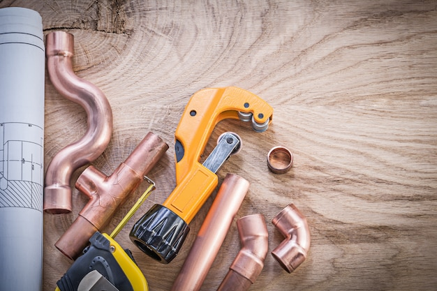 Construction plans measuring tape water pipe cutter fixtures on wooden board plumbing concept