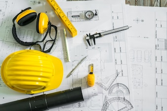 Construction plans with helmet and drawing tools on blueprints .