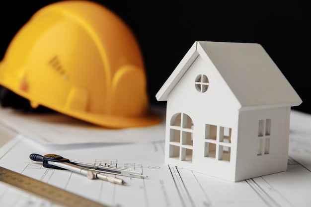 Construction plans with helmet and model of house closeup