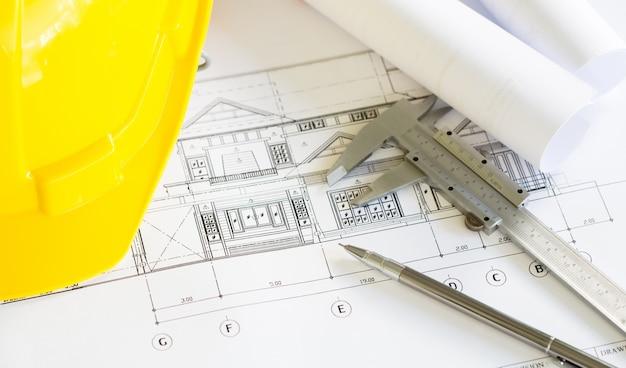 Планы строительства с желтым шлемом и чертежные инструменты на bluep
