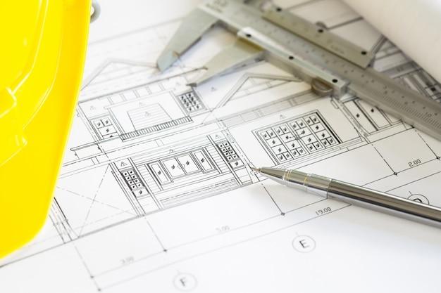 블루 헬멧에 노란색 헬멧 및 그리기 도구와 건설 계획
