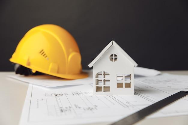 黄色いヘルメットと家のモデルの建設計画