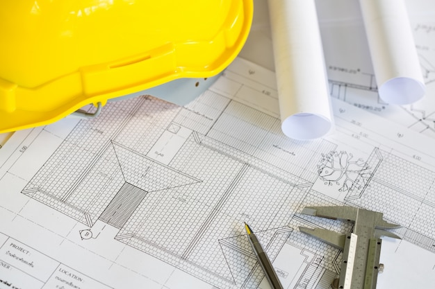 Construction plans with yellow helmet and drawing tools on bluep Free Photo