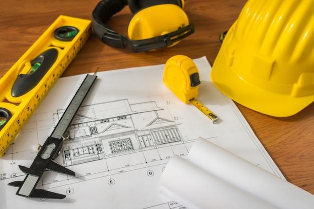 Piani di costruzione con il casco giallo e strumenti di disegno su bluep