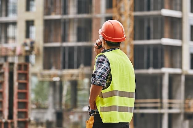 制服の赤い保護作業でプロの若いビルダーの建設プロセスの背面図