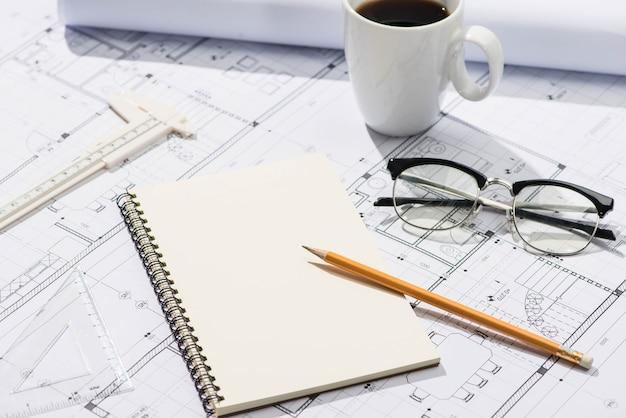 건설 프로젝트. 계획. 연필과 노트북으로 청사진을 엽니다.