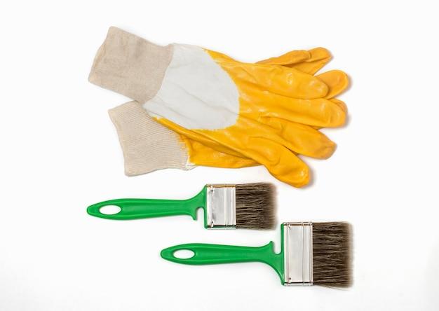 白地に2つの緑のブラシと黄色の建設用保護手袋。