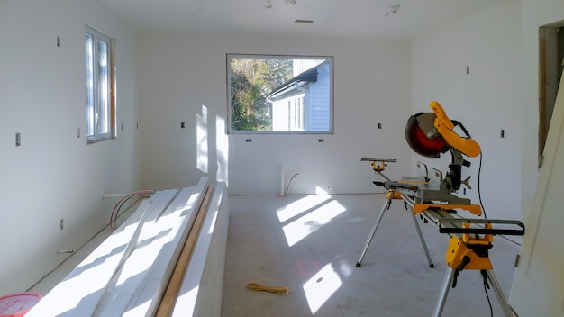 Construction remodeling home cutting wooden trim board on with circular saw.