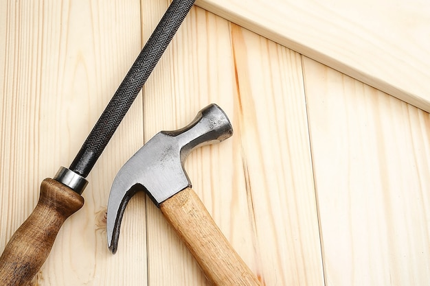 Construction and repair. carpentry. hammer and file tool on a wooden table