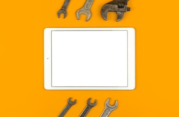 Концепция строительного ремонта макета, планшет с пустым белым экраном на столе с сервисными инструментами и оборудованием, желтый фон, вид сверху, плоская планировка и копия космической фотографии