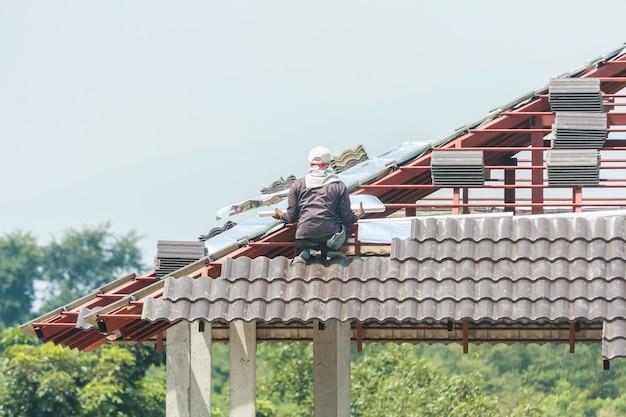 Строительный кровельщик, устанавливающий черепицу на строительной площадке дома