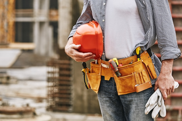 建設で働いているヘルメットとツールベルトを持つ男性ビルダーの建設安全トリミング画像