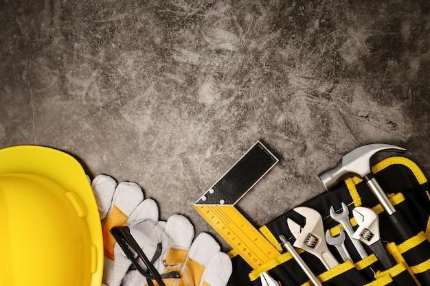 Строительное оборудование безопасности и инструменты на фоне бетонной текстуры. свободное место для текста
