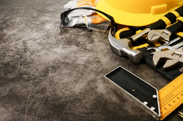 Construction safety equipment and tools on concrete texture background.