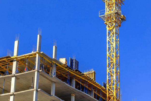澄んだ青い空の背景写真の建設現場と建設タワークレーン