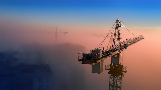 夜明けの建設現場。朝の太陽の霧の上にタワークレーン。ドローンビュー