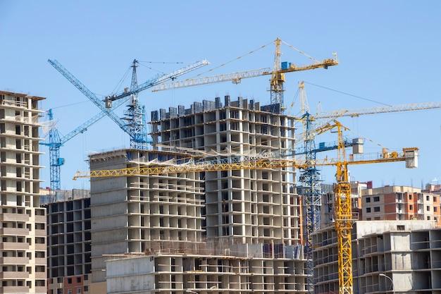 建設現場の背景。吊り上げクレーンと新しい高層ビル。タワークレーンと未完成の高層ビル。多くのクレーン